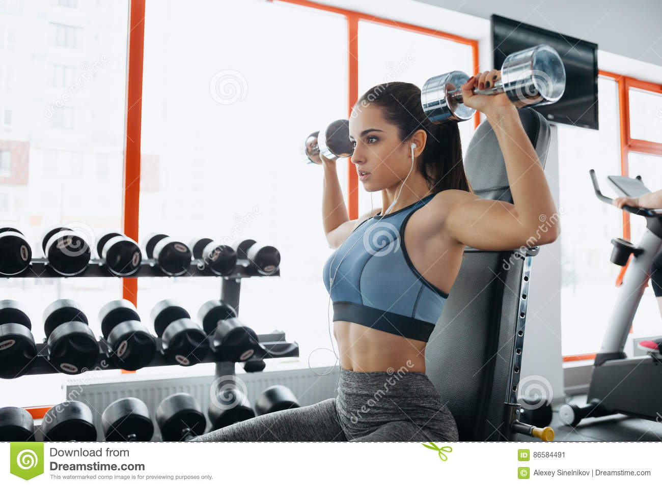 Beautiful sporty woman doing power fitness exercise at sport gym.