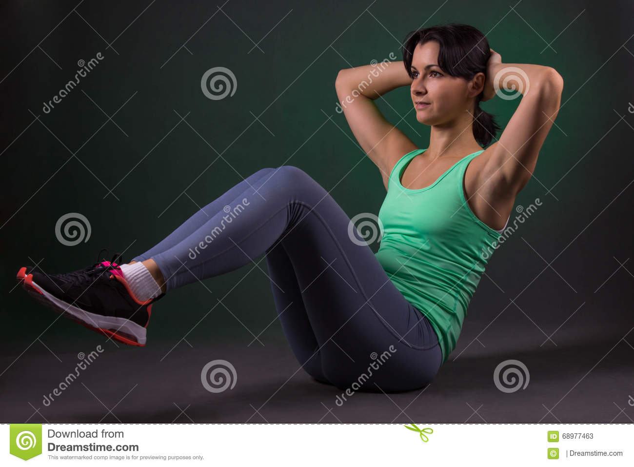 Beautiful sporty woman, fitness woman doing exercise on a dark background with green backlight