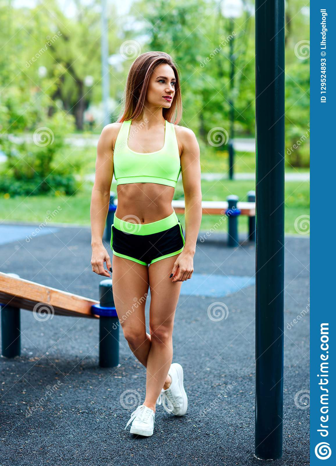 Sporty woman with perfect athletic body posing on sportsground.