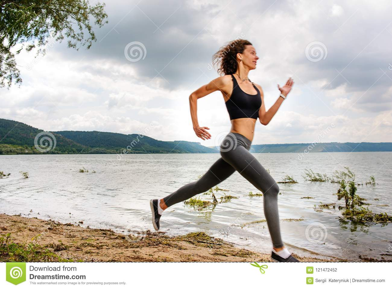 A beautiful sporty woman runing on the shore of a lake in sports