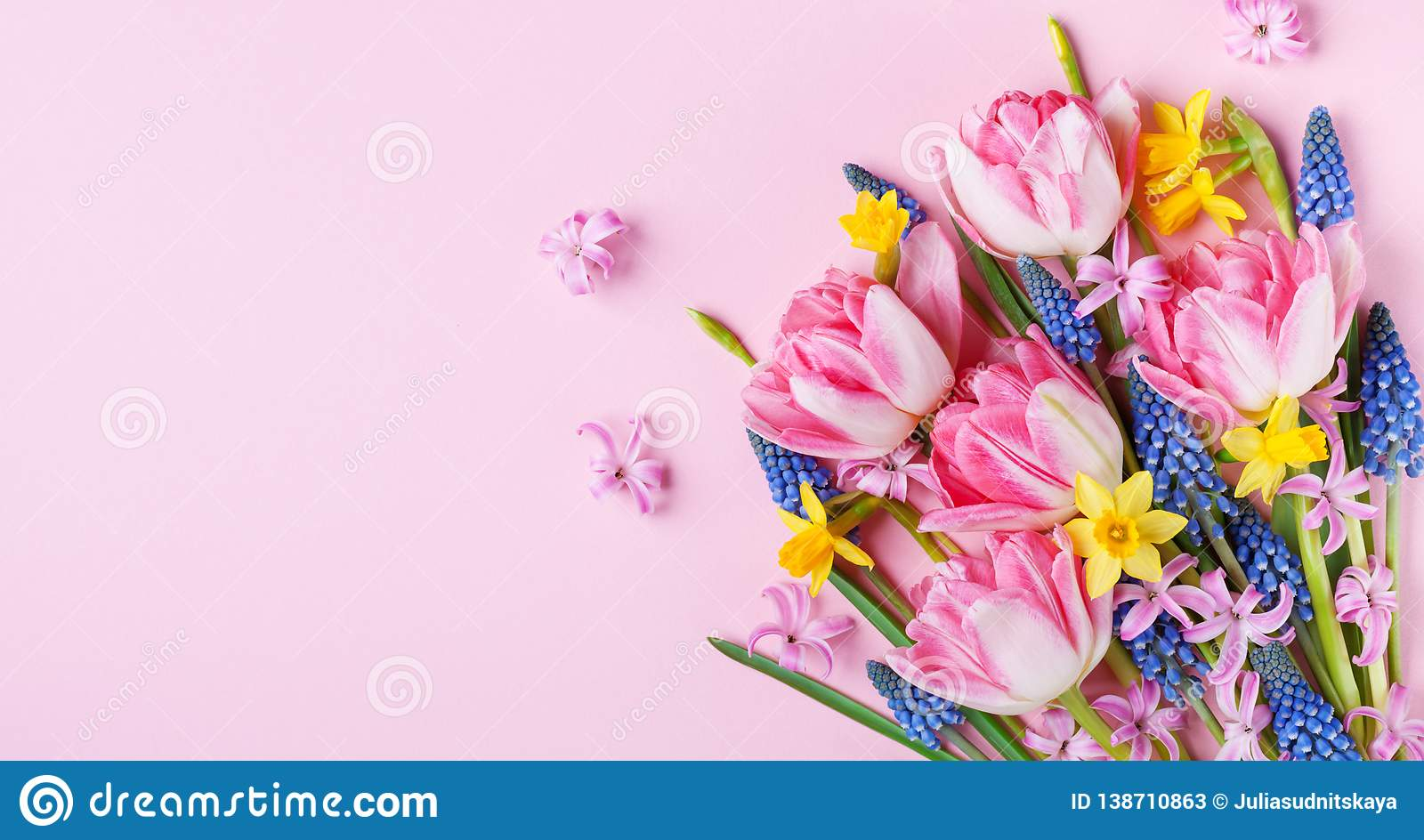 Beautiful spring flowers on pastel pink table top view. Greeting card or banner for International Women Day. Flat lay