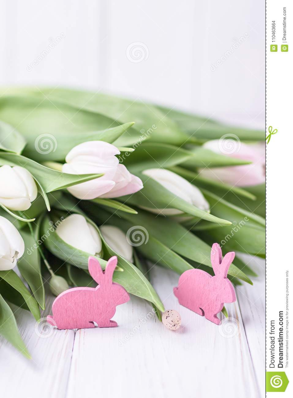 Beautiful spring flowers tulips and pink Easter bunnies on a white background. Free space