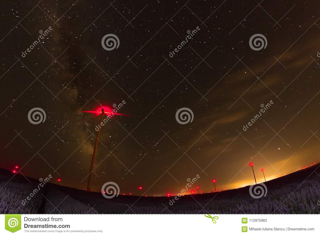 Beautiful starry night sky with milky way over a field of lavender and red lights of wind turbines