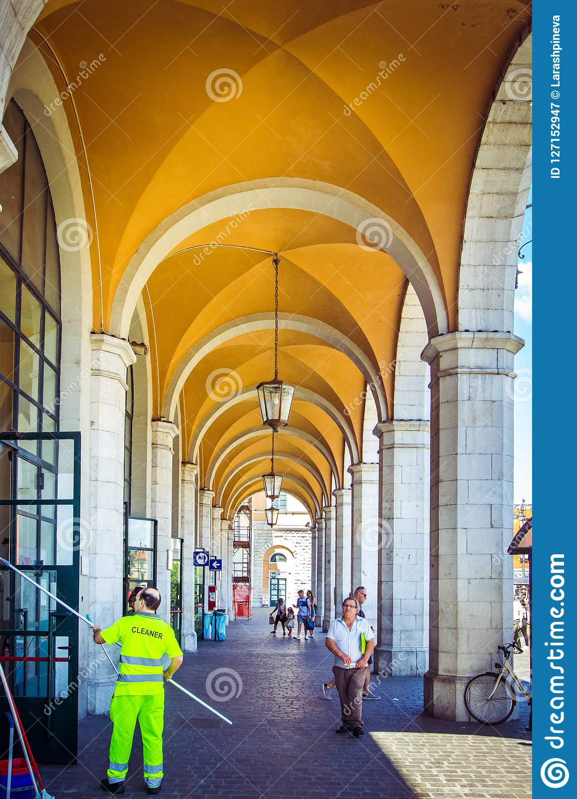 Beautiful station in Pisa with white pillars and yellow arches, with working cleaners and tourists, Pisa, Italy