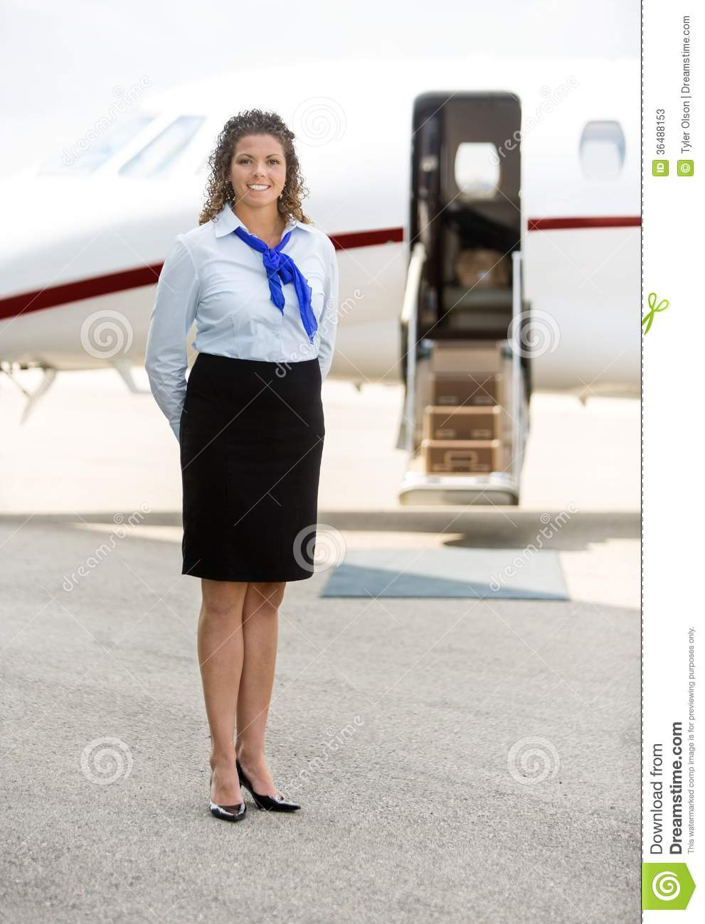 beautiful stewardess standing against private jet stock