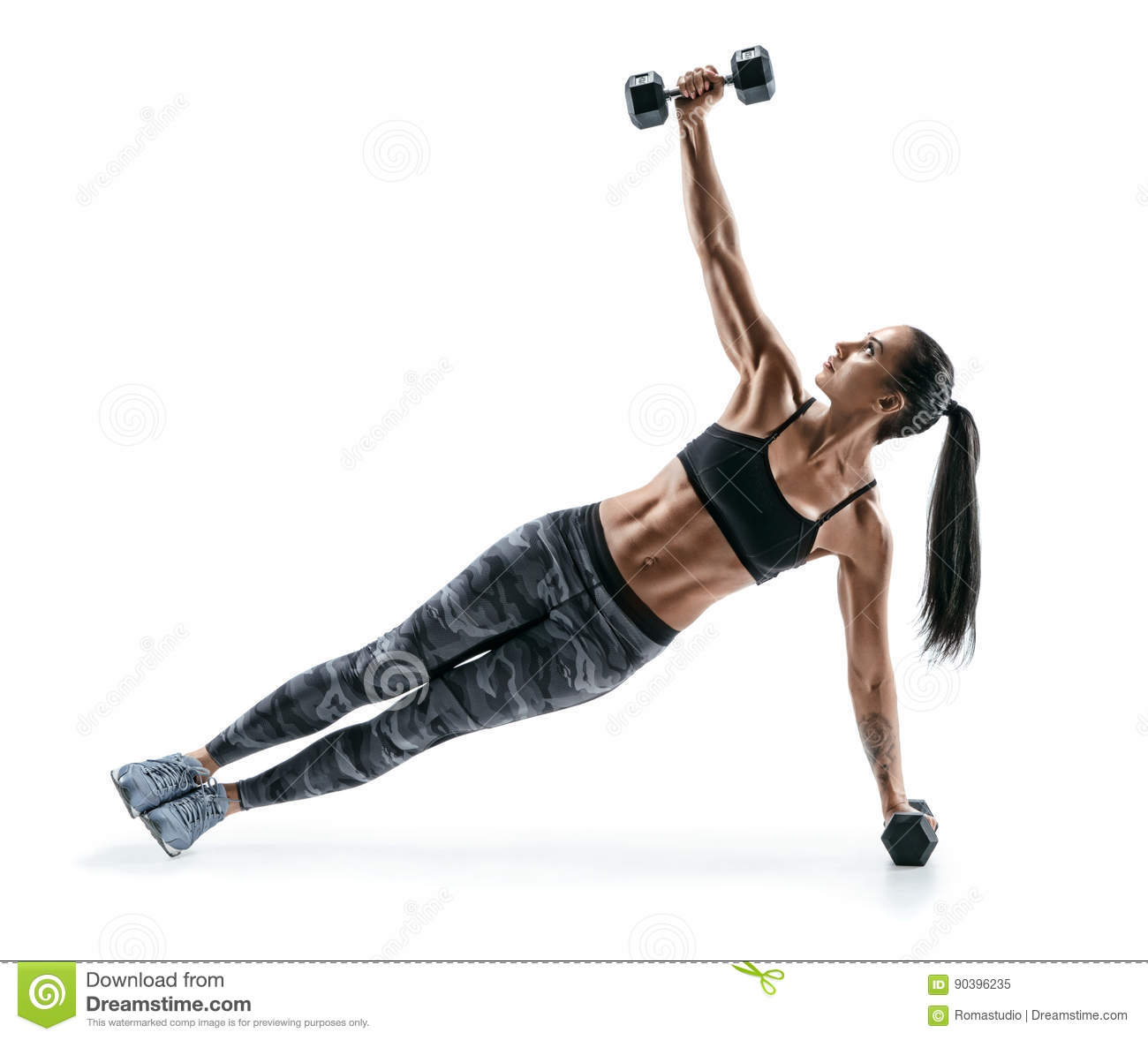 Beautiful strong woman doing fitness plank position exercises with dumbbells