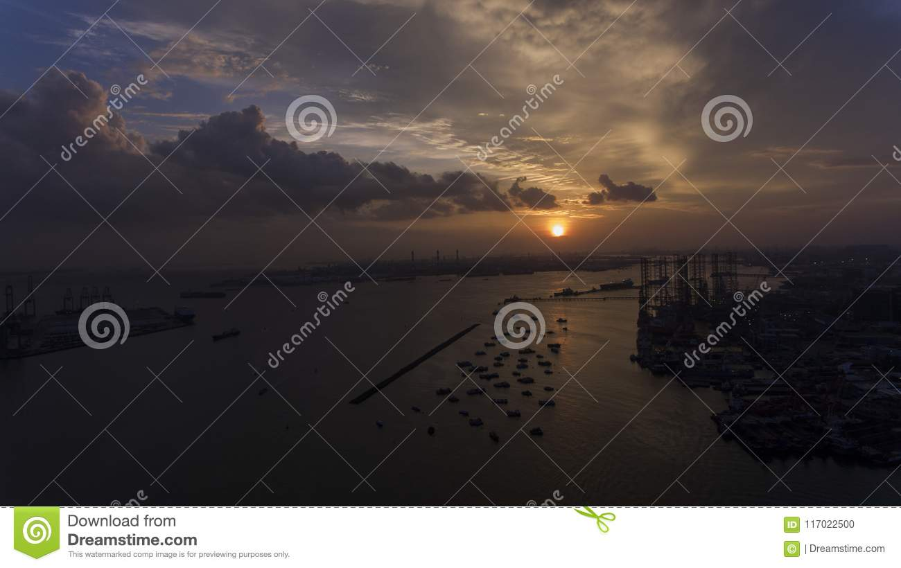 Beautiful, stunning sunset over the water, over boats in an industrial looking dock or port.