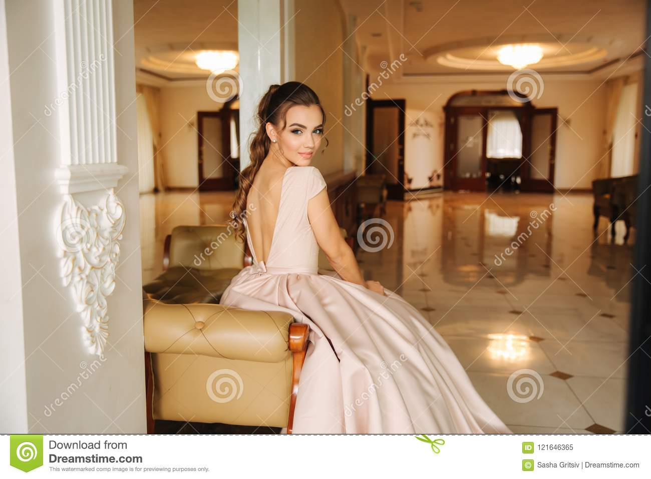 3573dffd73 Beautiful stunning young lady in amazing dress sitting on luxury armchair.