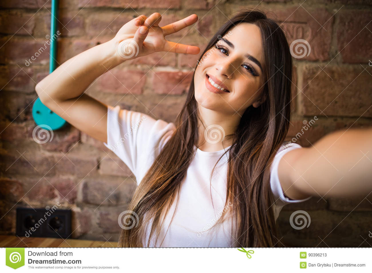 Beautiful stylish girl making selfie with victory gesture on brick background