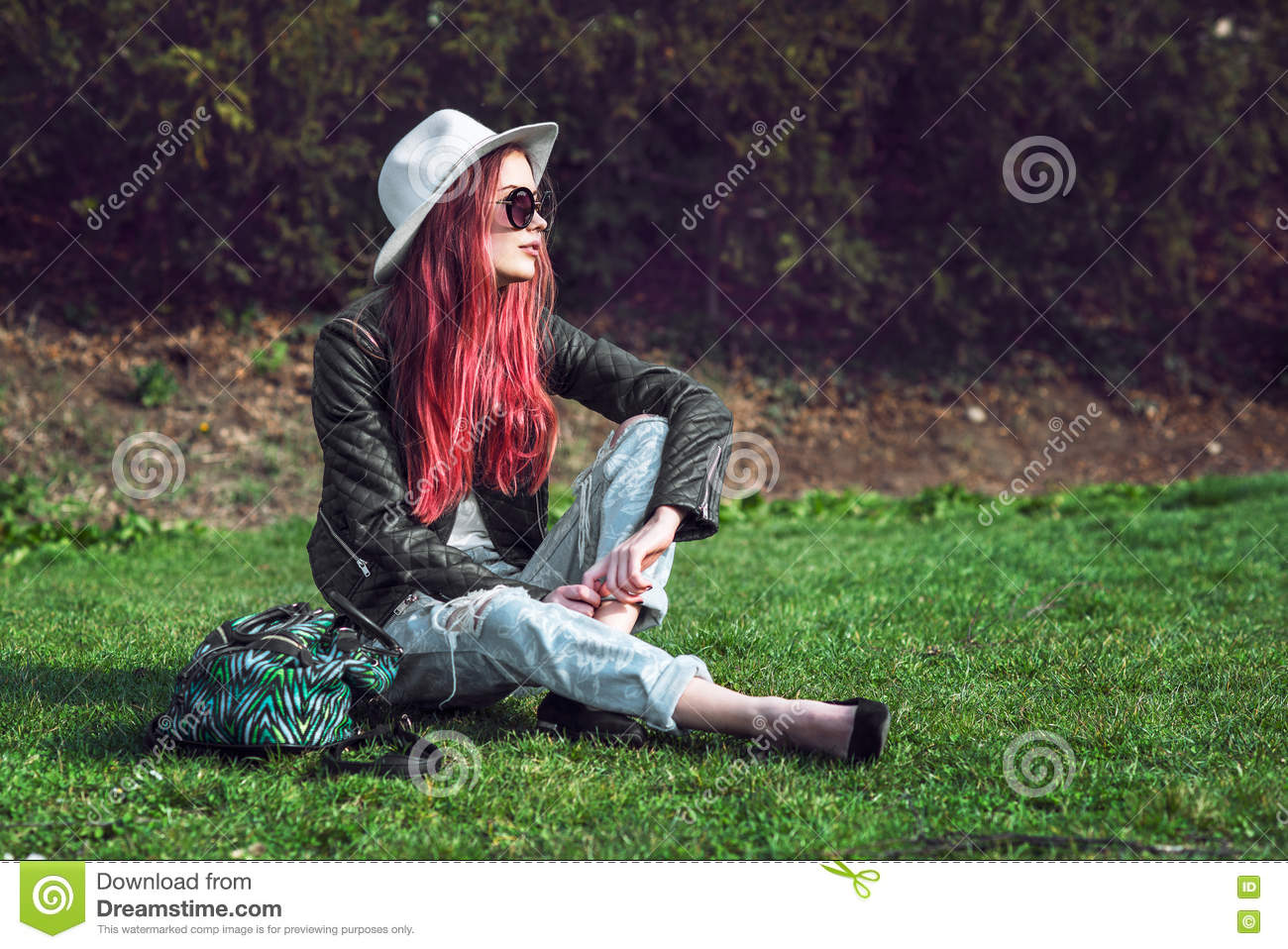 Beautiful stylish red haired fashion hipster model woman sitting outdoors on green grass at park wearing sunglasses, hat and black