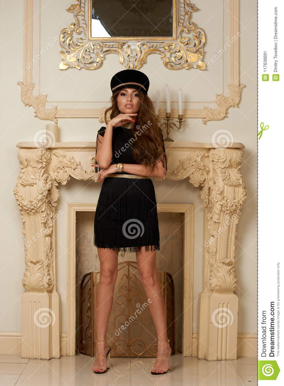 15f490e088d Beautiful stylish slim tall tanned young woman in short black dress and cap  posing in luxury interior
