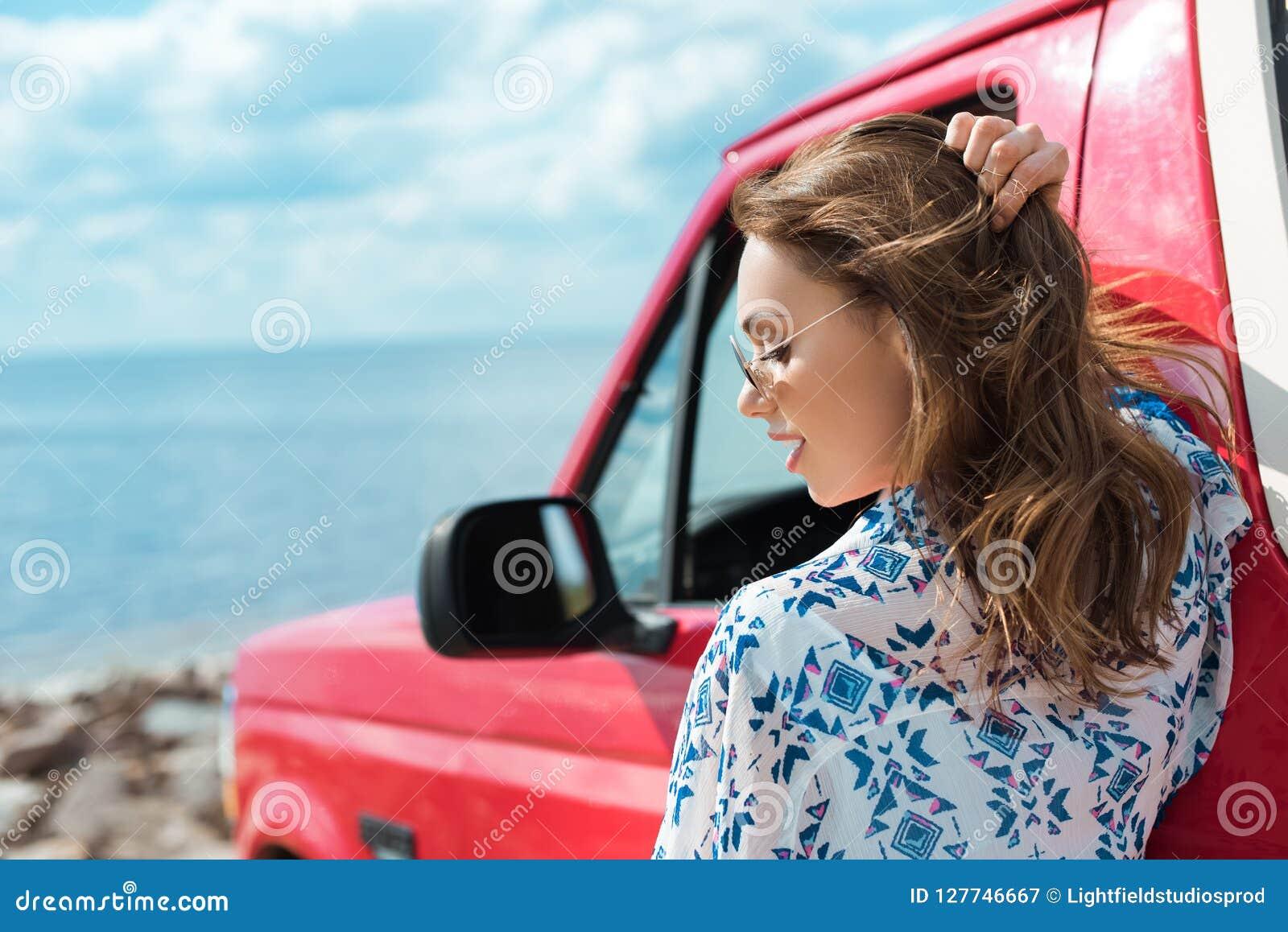 beautiful stylish woman at car during road trip