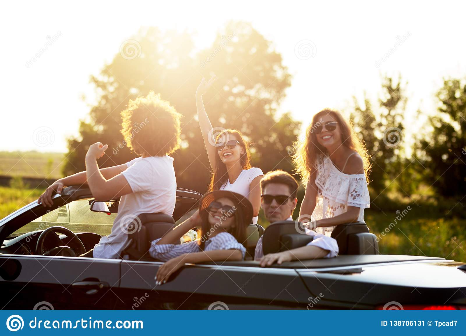 Beautiful stylish young girls and guys in sunglasses are sitting and laughing in a black cabriolet on a sunny day.