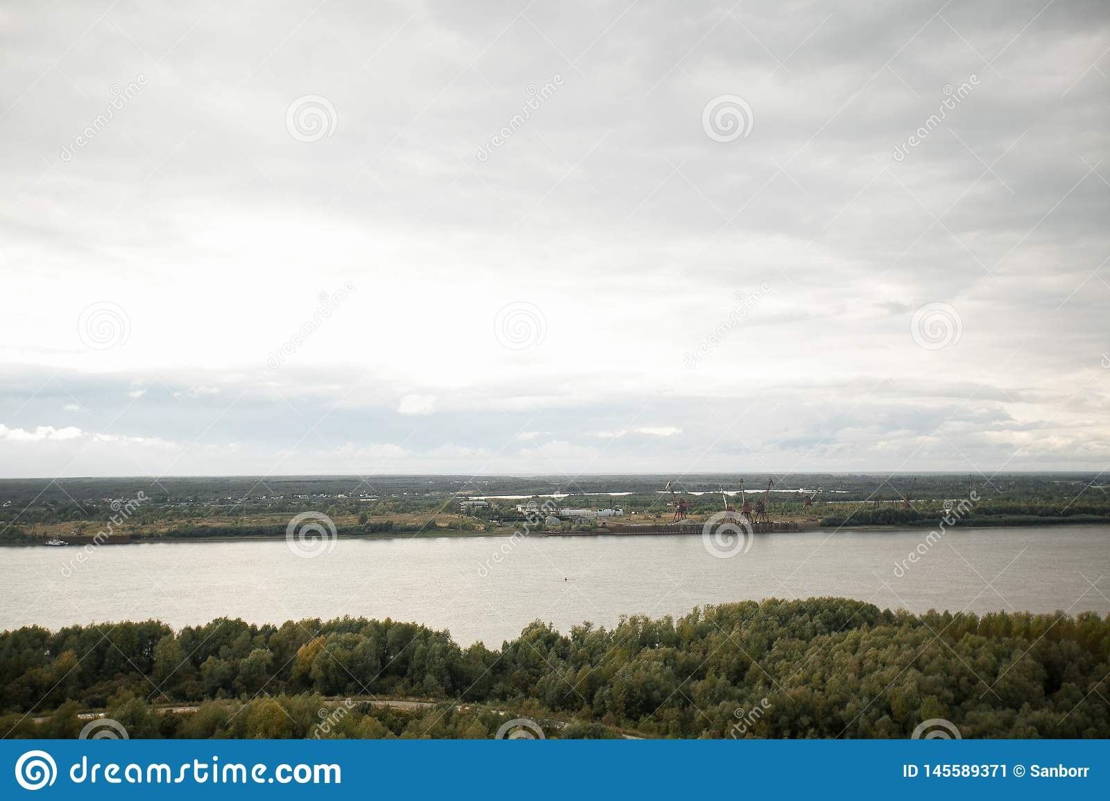 Beautiful summer landscape. The forest along the broad river. Nearby there is an industrial base and a small village