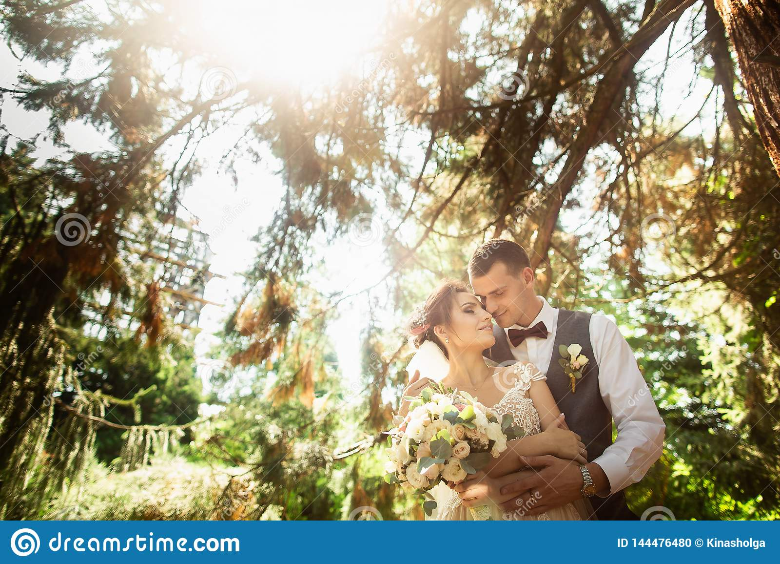 Beautiful sunny day. Wedding couple posing on the background of nature
