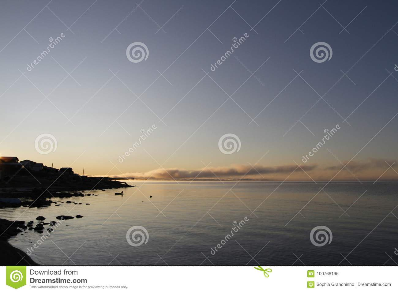 Beautiful sunrise over an arctic lake with fog on the horizon