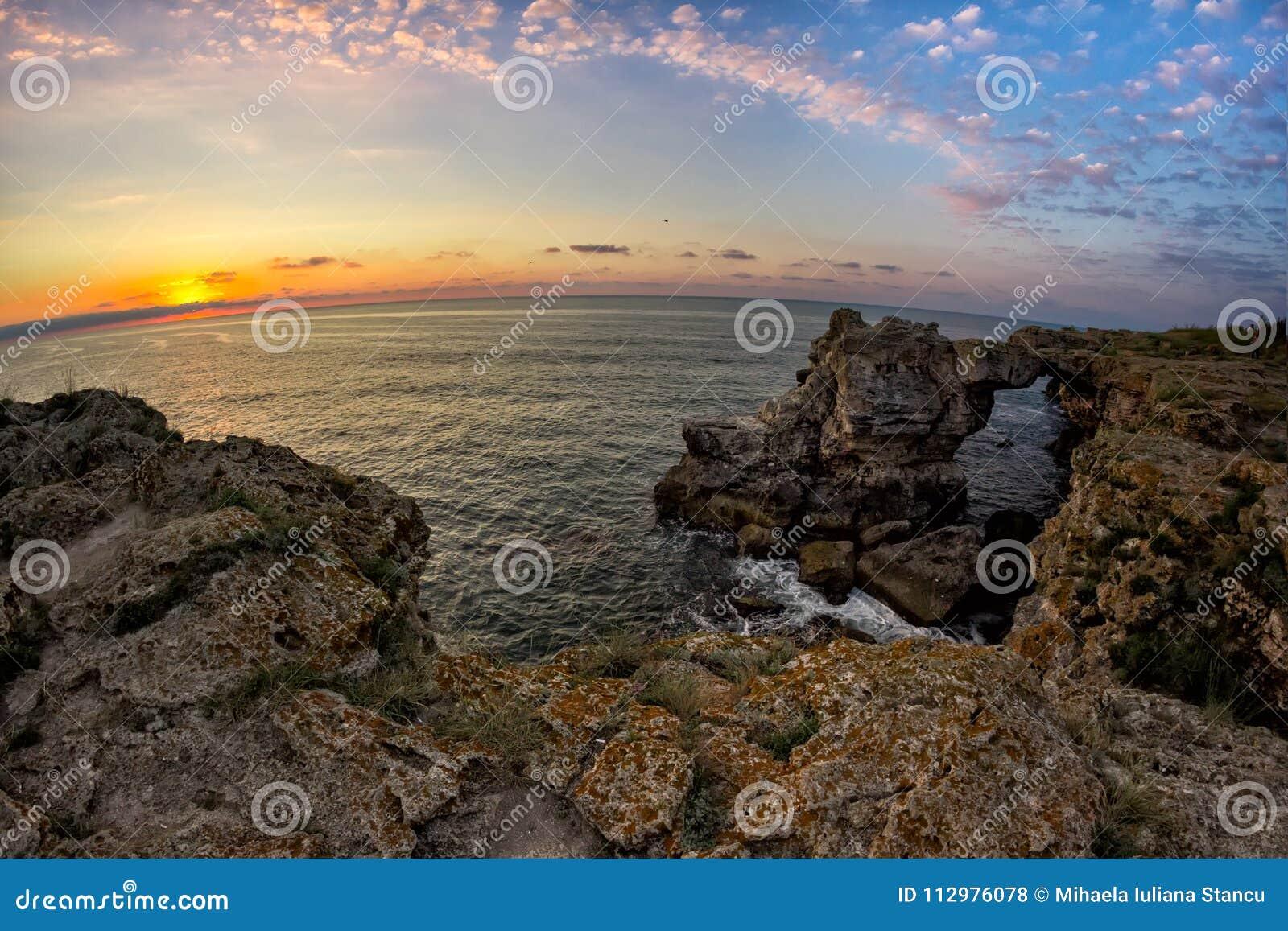 Beautiful sunrise over the Black Sea with rocks on the shore