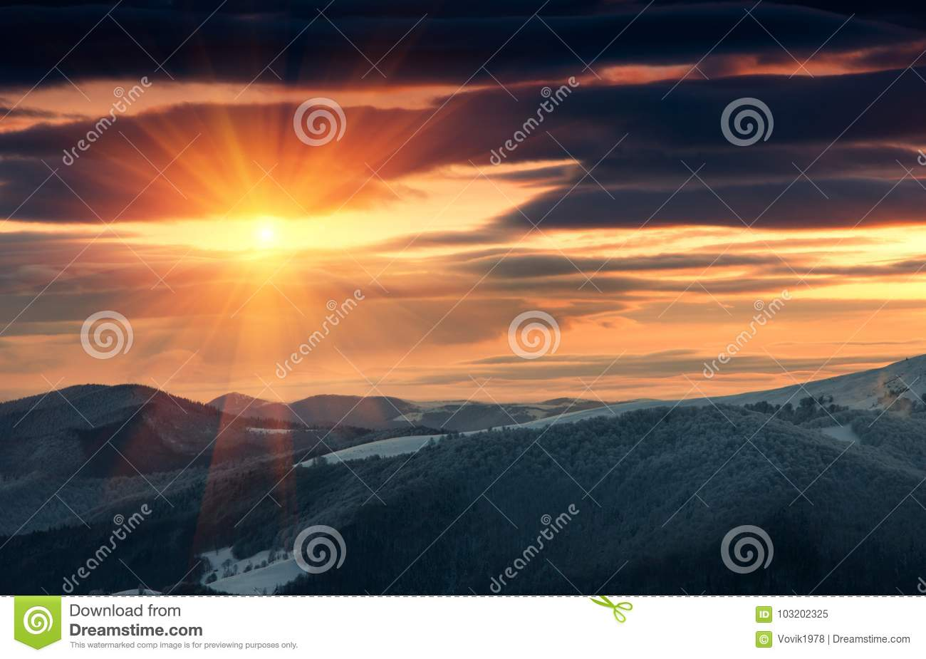 Beautiful sunrise in the winter mountains. Dramatic cloudy over sky.