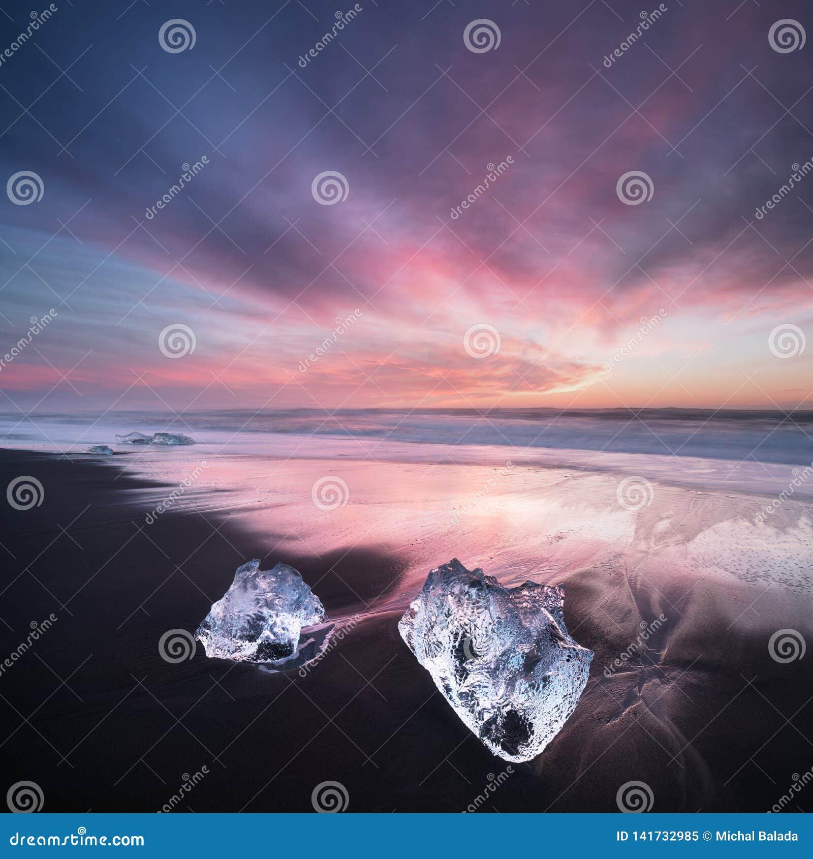 Beautiful sunset over famous Diamond beach, Iceland. This sand lava beach is full of many giant ice gems, Jokulsarlon.