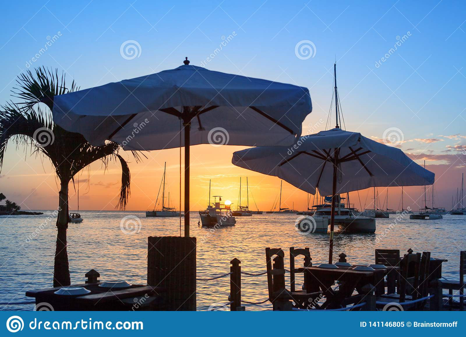 Beautiful sunset on the sea beach cafe or restaurant, boats, ships and yachts silhouettes on water background