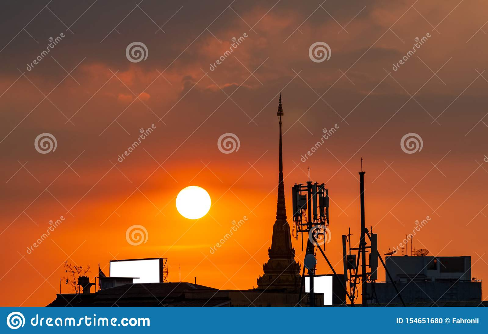 Beautiful sunset sky over the city. Silhouette temple building and telecommunication tower. Antenna on sunset sky background.