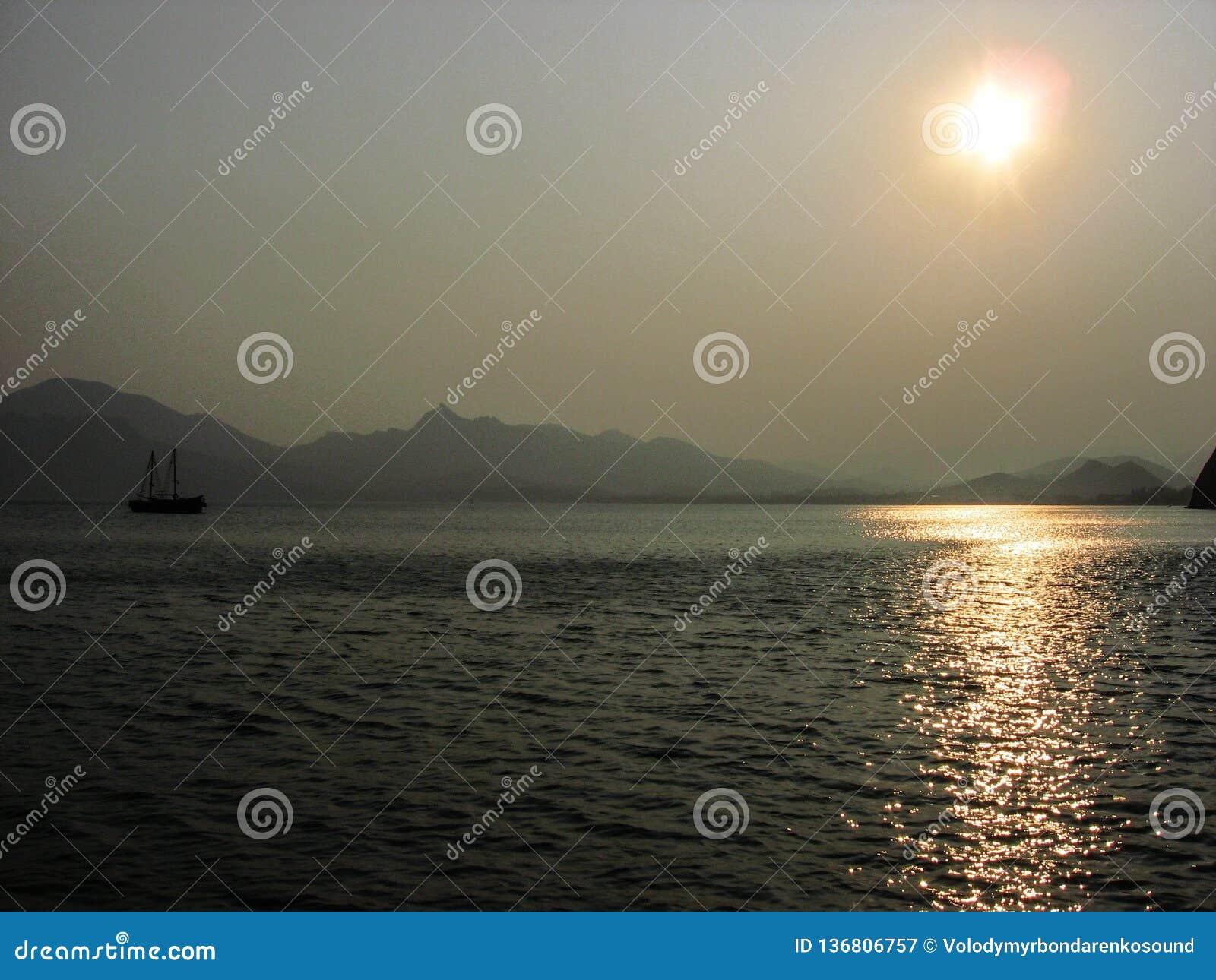 Beautiful sunset, small ship sailing in the ocean. Odessa, Ukraine