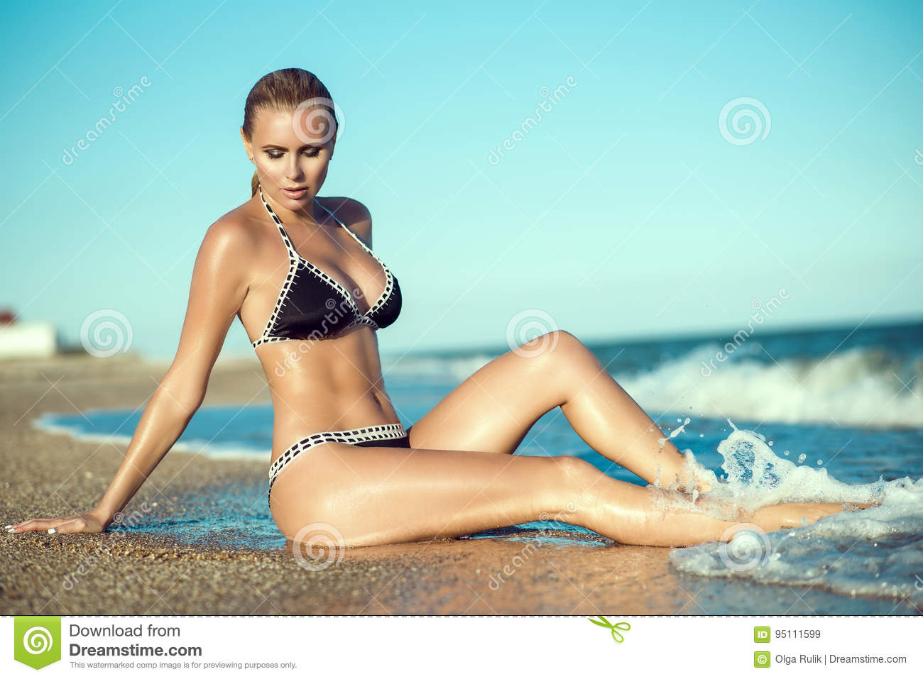 Beautiful suntanned glam blond woman with wet skin and hair sitting on the beach and enjoying, her long legs washed by the waves