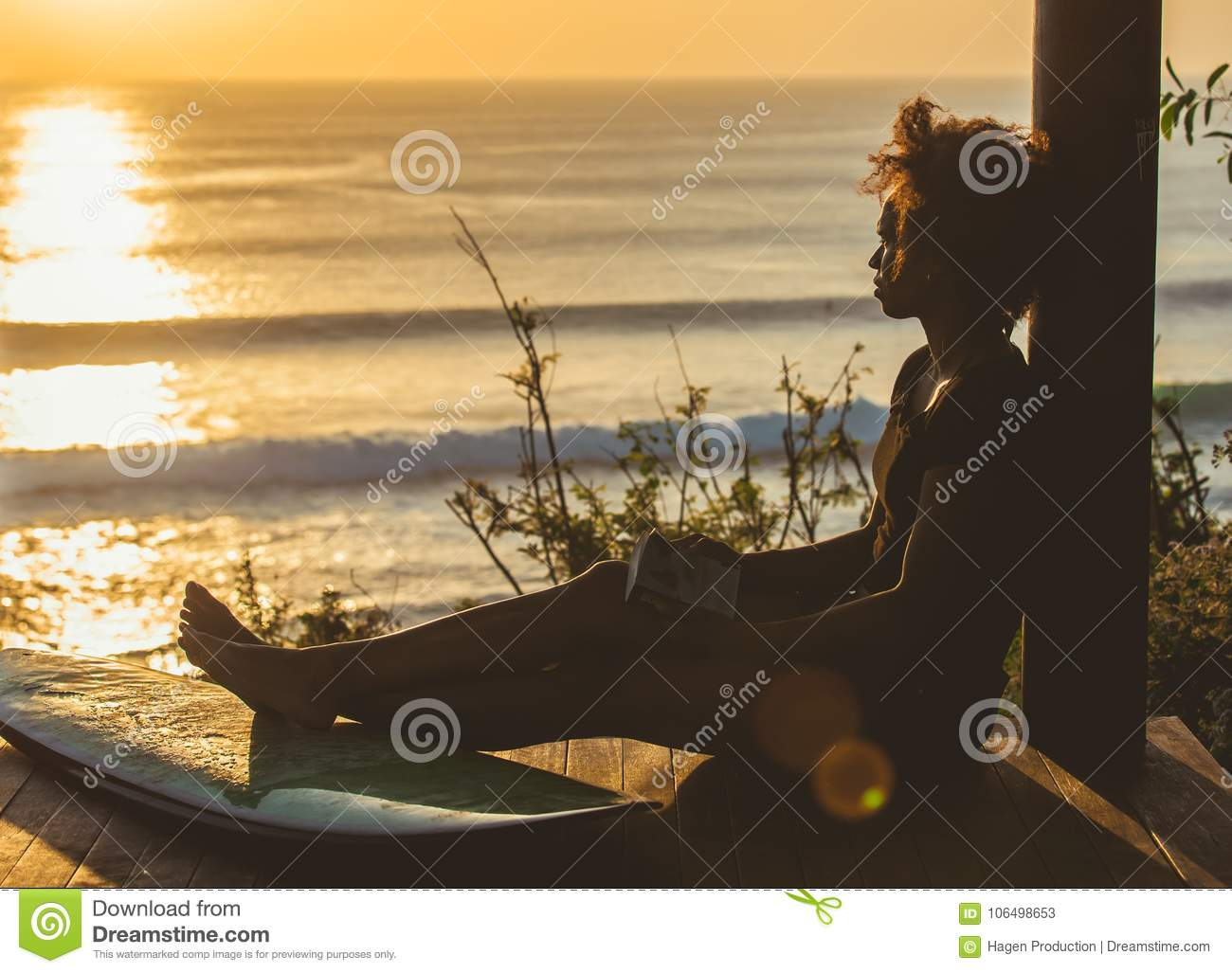Beautiful surfer girl with afro hair style reading book on top of the cliff at sunset