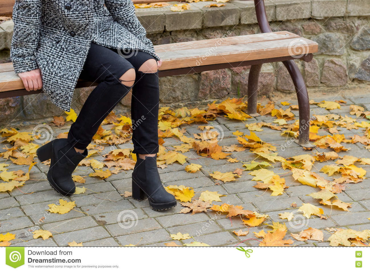 Beautiful sweet girl with the big sad eyes in coat sitting on the bench in the fall among the fallen yellow leaves autumn bright