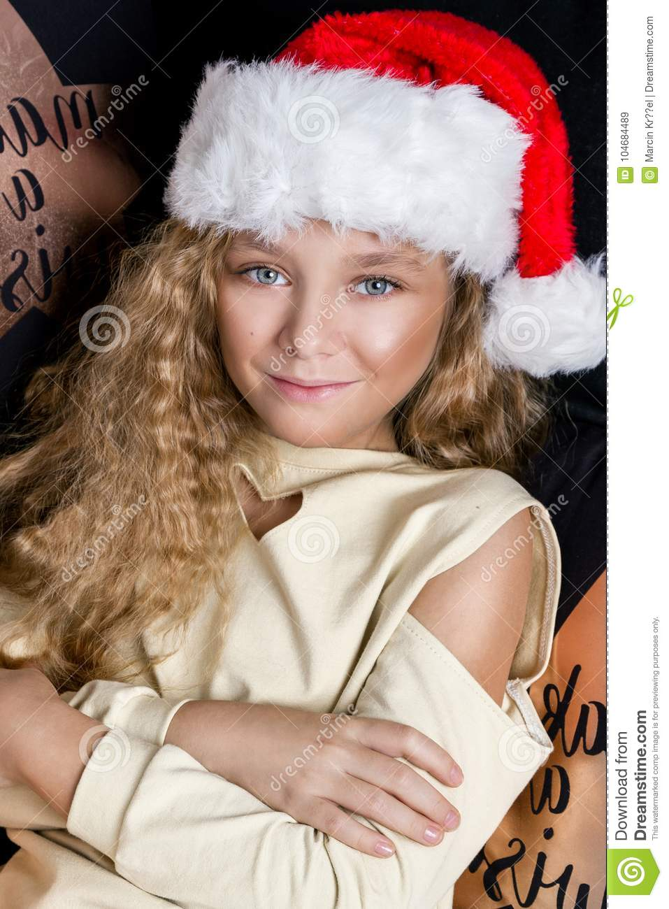 e6b1b252e Stunning beautiful little girl with long blond hair lying on a bed in a  Santa Claus hat and joyfully look into the lens at Christmas time