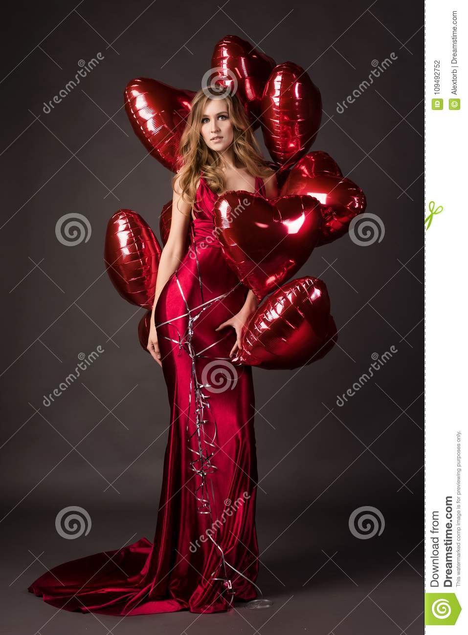cd32c73b4 Beautiful tall slender blond girl wearing a deep neckline red satin dress  posing with red balloons in the shape of a heart. Valentine`s Day,  holidays, ...