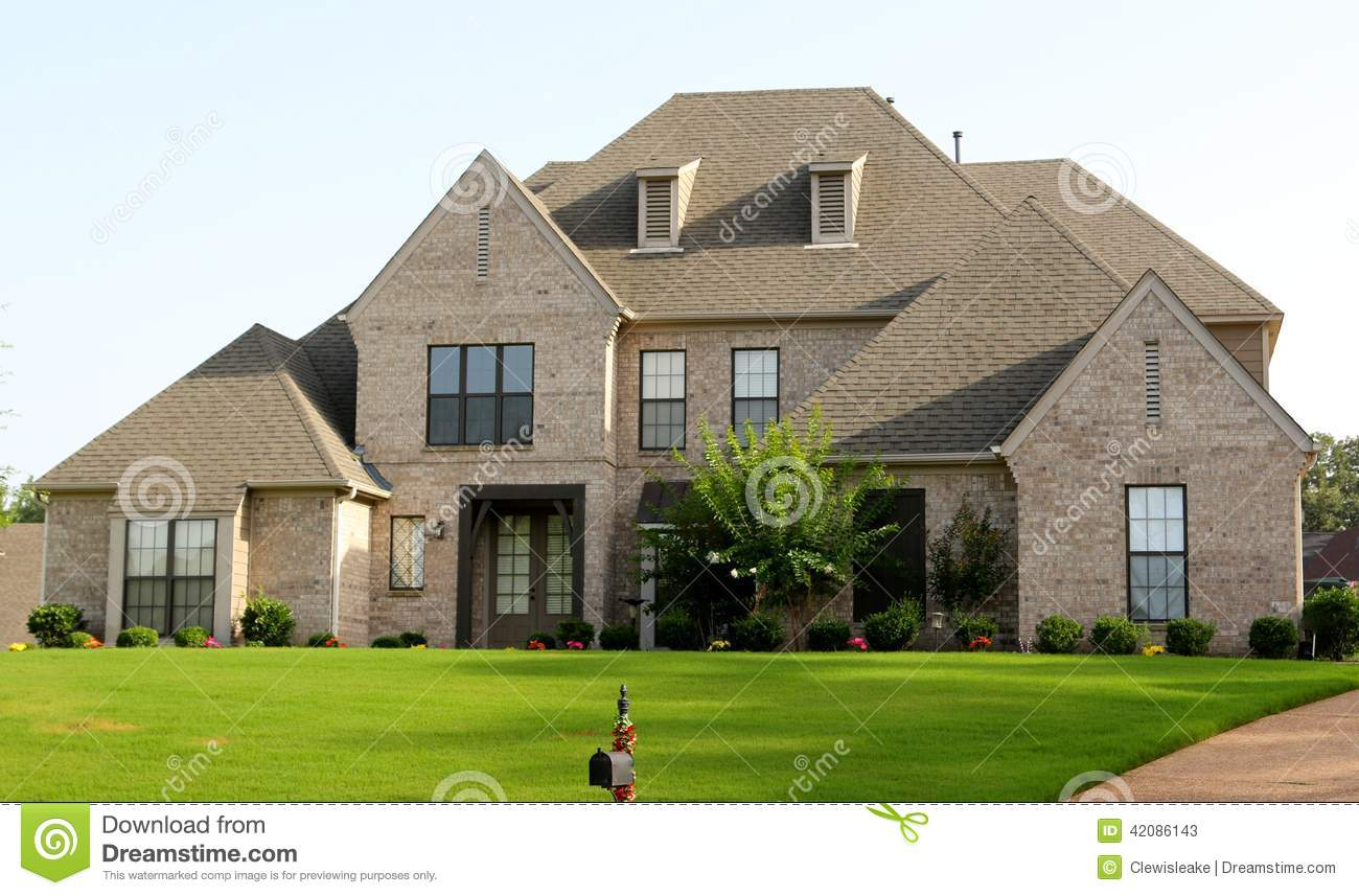 Beautiful tan brick and stucco suburban home stock image for Home tanner