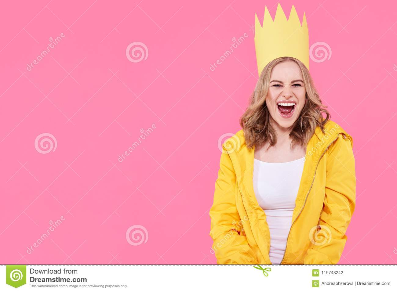 Beautiful teenage girl in bright yellow jacket and party hat shouting with excitement. Attractive cool woman fashion portrait.