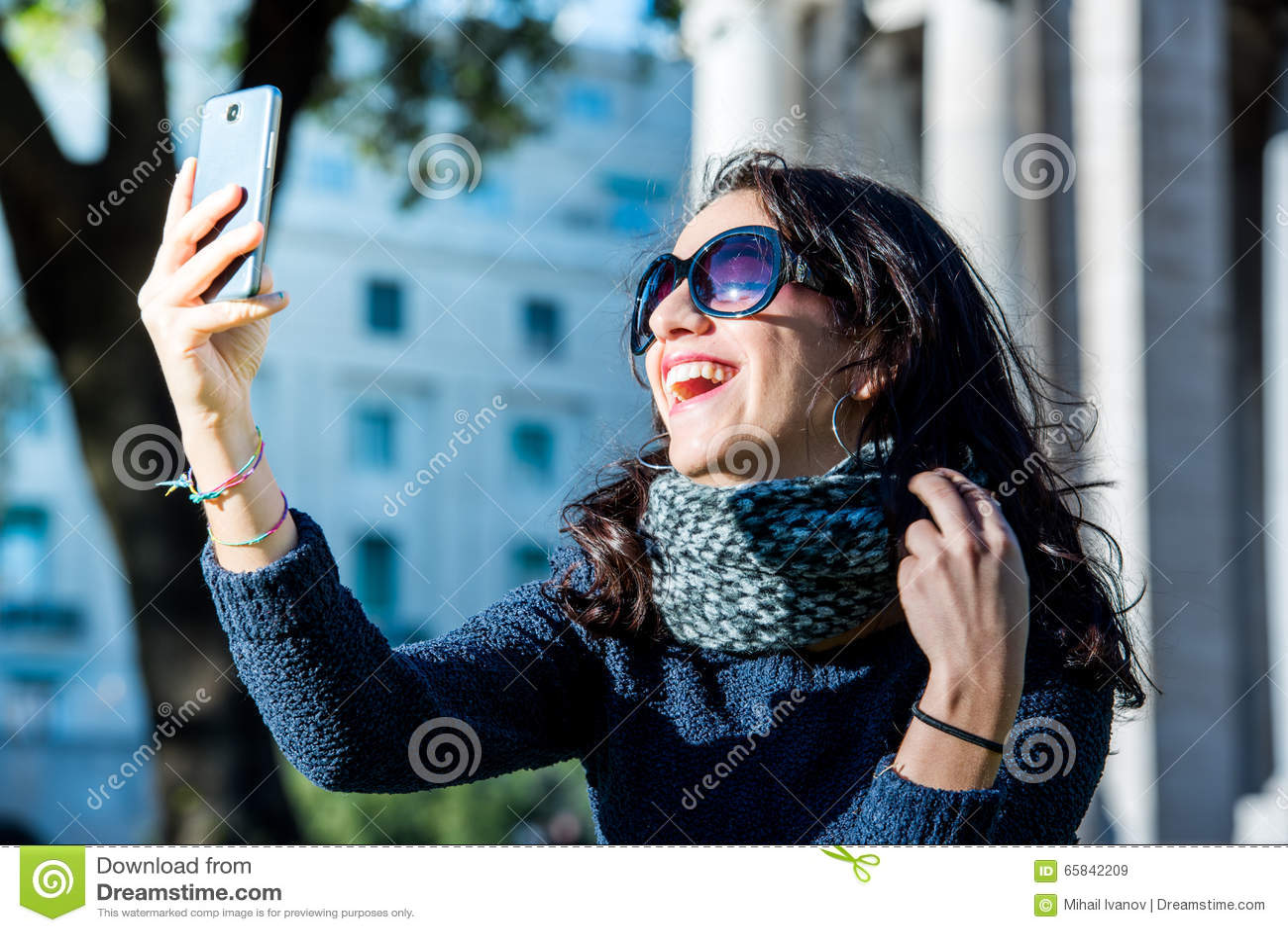 Beautiful teenage girl with dark hair and sun glasses taking selfies and laughting - close shot