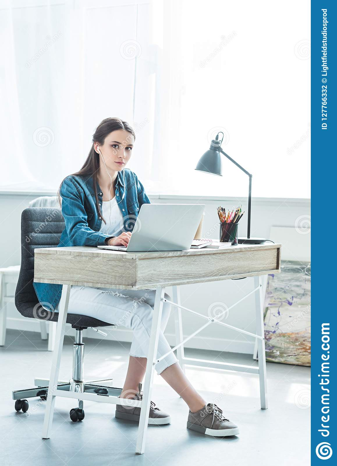 beautiful teenage girl in earphones using laptop and looking at camera while sitting at desk