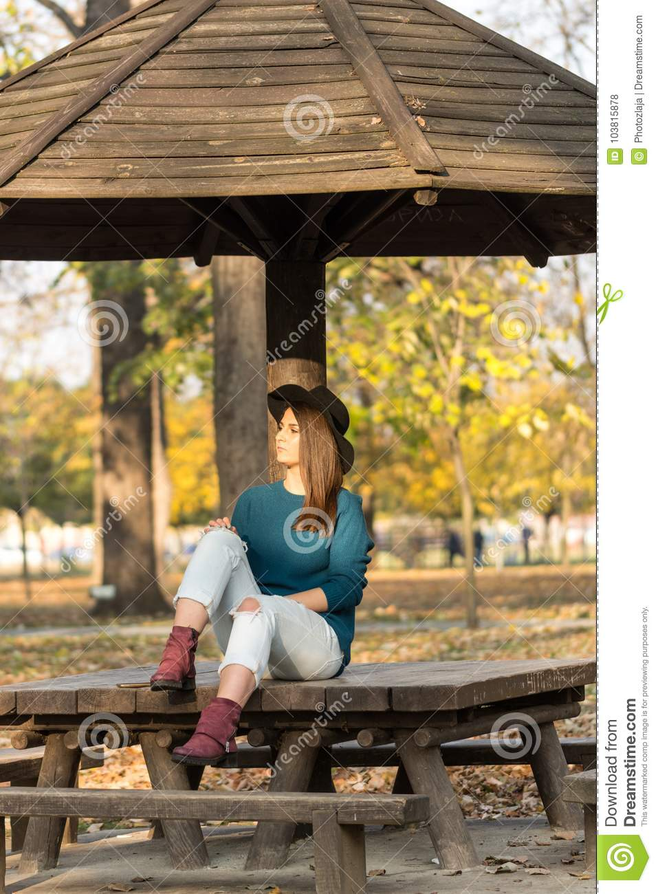 bb84634e33977 Beautiful teenage girl sitting on the park bench with black hat blue sweater  and ripped jeans with blurred autumn leaves in the background.