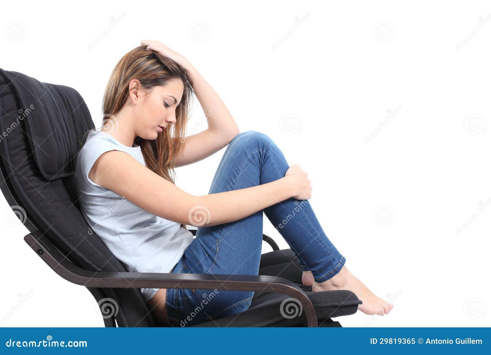 Beautiful teenager worried sitting on an armchair