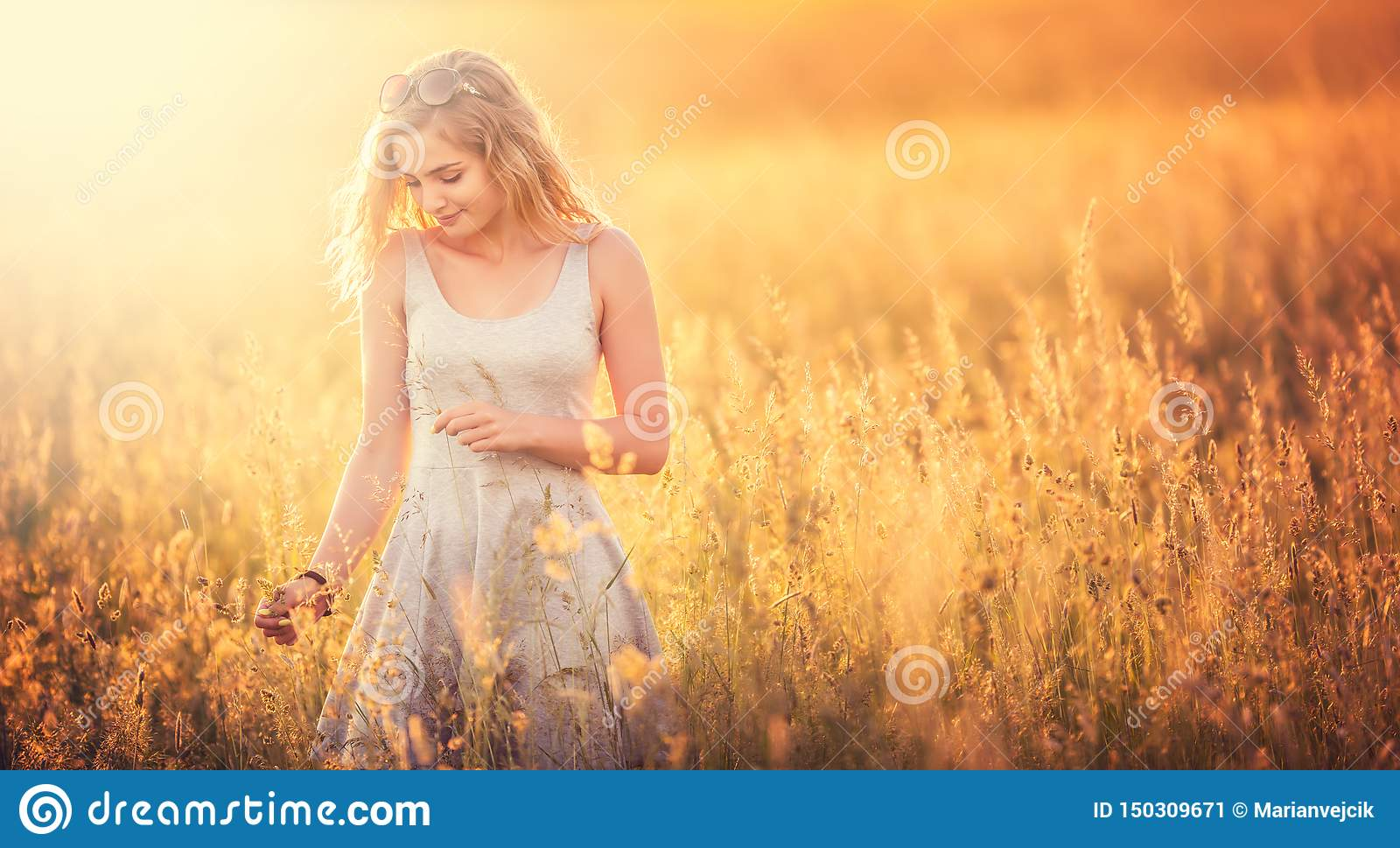 Beautiful tender blonde young girl standing at summer meadow in gray sundress. Free happy woman enjoying nature