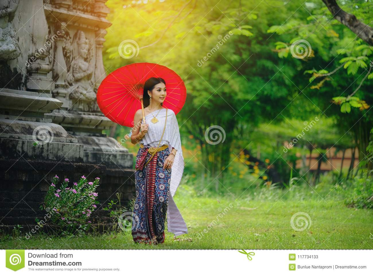 Beautiful Thai girl in traditional dress costume red umbrella as