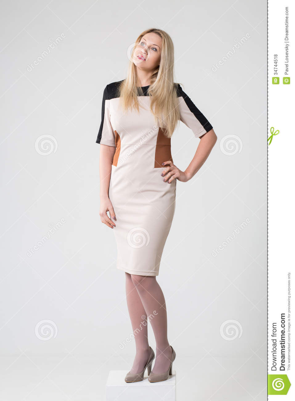 Beautiful thoughtful girl in a beige dress and shoes