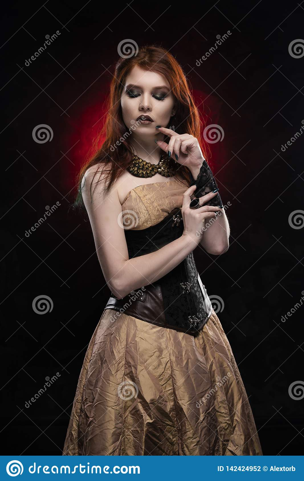 A beautiful thoughtful redhead cosplay girl wearing a Victorian-style steampunk dress and corset. Portrait. Black and red