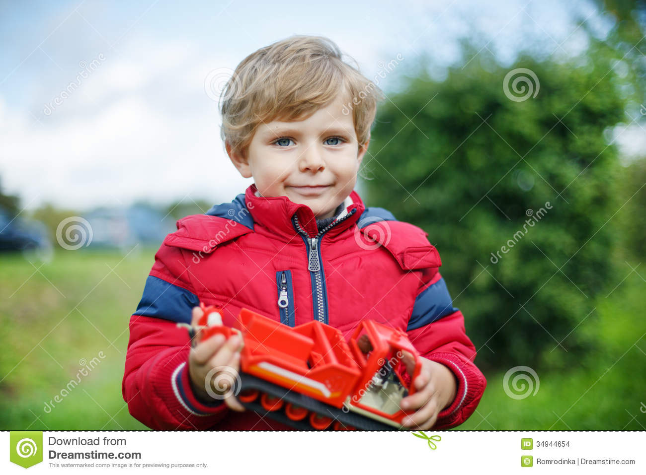 Beautiful Toddler Boy In Red Clothes With Ship Toy In