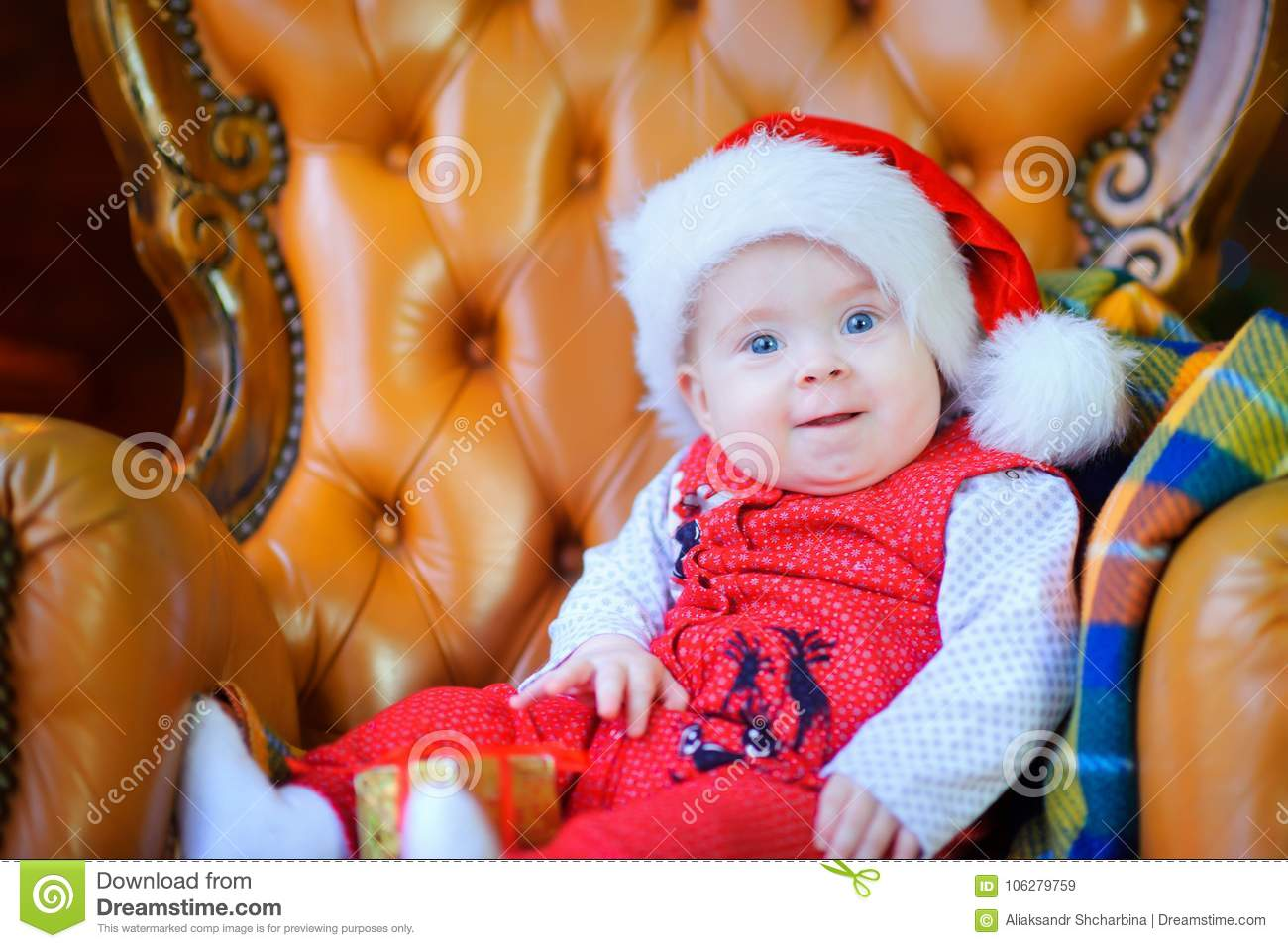 d199bc584a0 Beautiful toddler in santa claus cap sits on chair smiling and looks at  camera