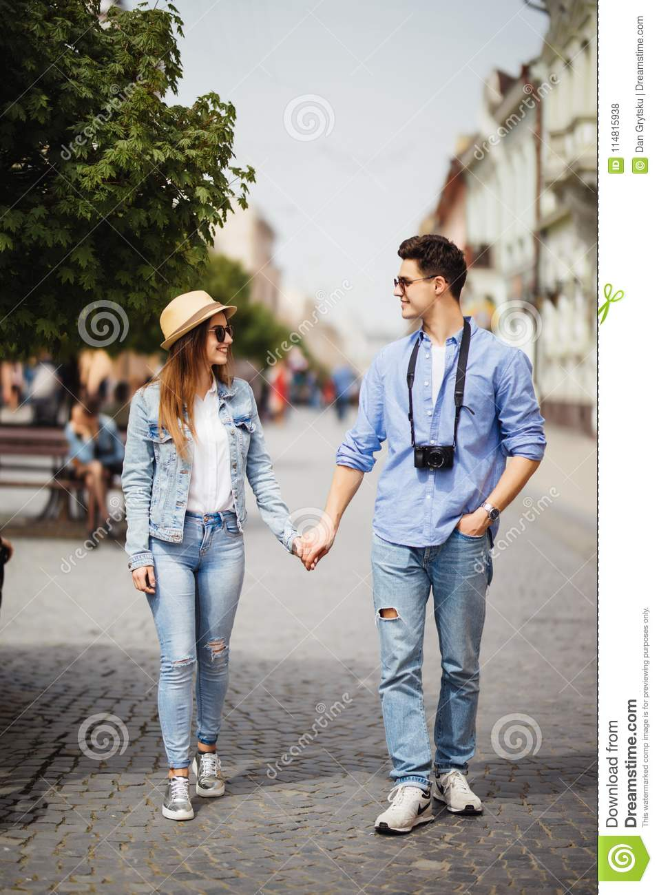 Beautiful Tourist Couple In Love Walking On Street Together. Happy Young Man And Smiling Woman Walking Around Old Town Streets, Lo