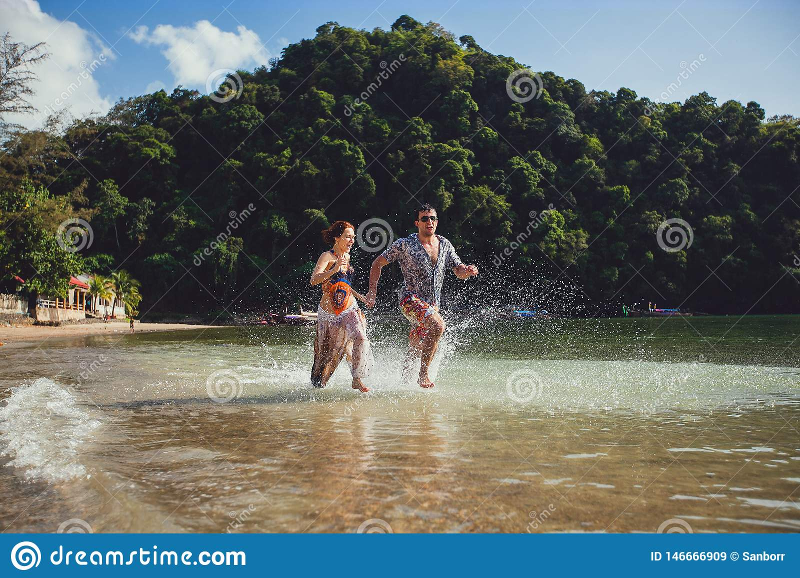 Beautiful tourist young couple holding hands together running along the beach shore with mountains and blue sea water and sky,