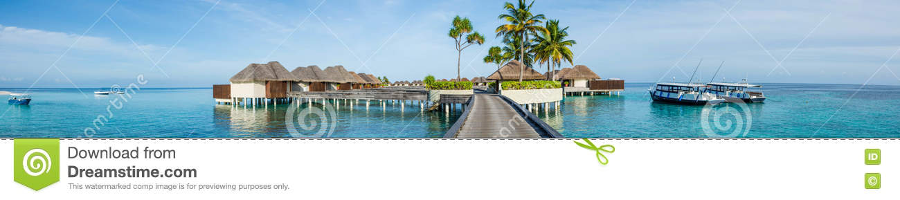 Beautiful tropical beach panorama of bungalos with bridge near the ocean with palms trees and boats at Maldives