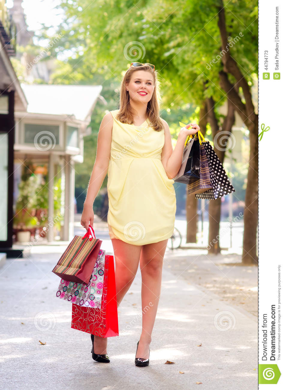 Beautiful urban girl walking down the street after shopping on sunny
