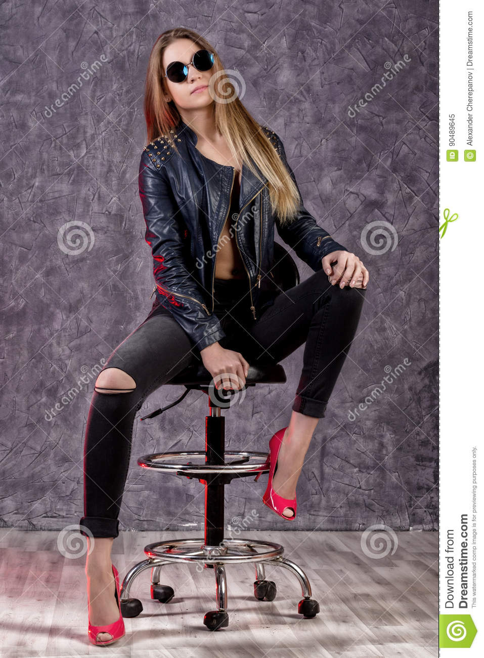 Beautiful urban trendy girl in black leather jacket and jeans posing on a high chair