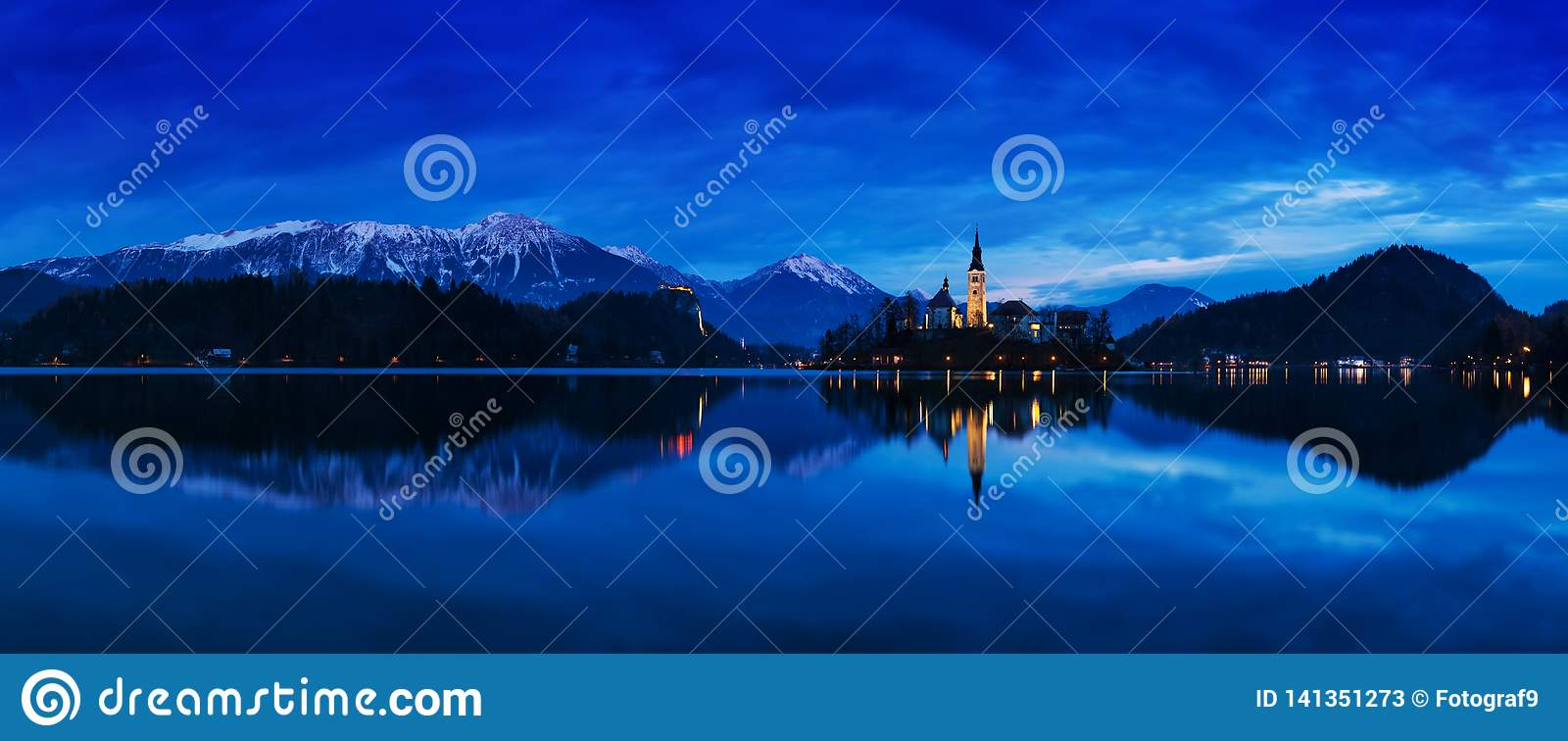 Beautiful view of famous Bled Island with Catholic Church at scenic Lake Bled with Bled Castle Blejski grad and Julian Alps
