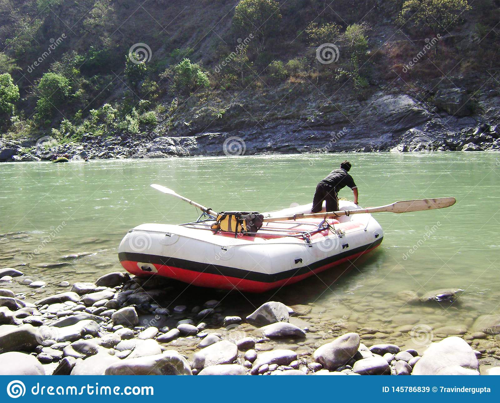 Flowing River, Boat with Man and Mountain